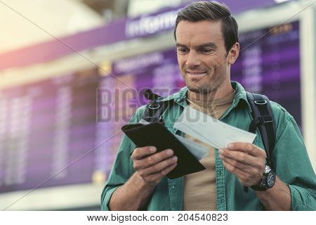 Checking flight details. Cheerful guy is holding tickets and smiling while standing in modern airport with information board on background. Copy space in the left side