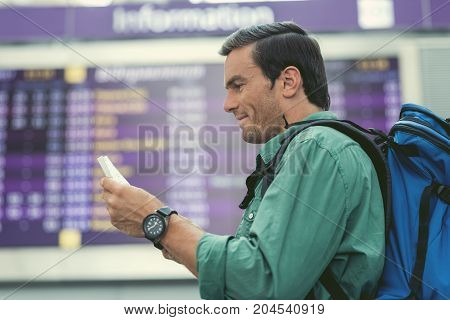 Happy journey. Profile of delightful man is holding tickets and expressing gladness while standing in modern airport with information board on background
