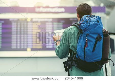 Casually dressed man with backpack and tickets is looking at timetable while standing in airport terminal hall. Back view. Copy space in the left side