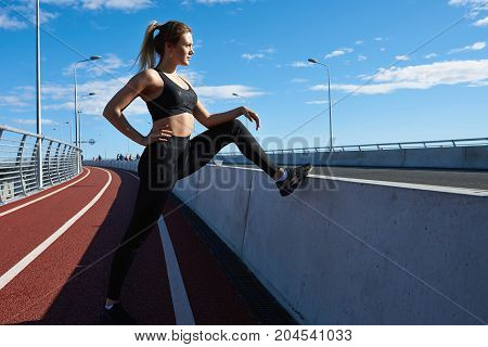 Outdoor summer sideways shot of confident blonde young woman with ponytail wearing black sneakers top and leggings stretching along pathway before run. Fit athletic girl exercising in the morning