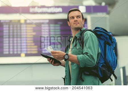 Travel lifestyle. Low angle of positive adult traveler with backpack is holding tickets and looking aside thoughtfully while standing in modern airport. Copy space in the left side