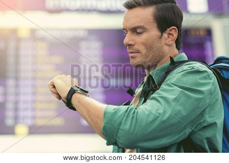 Checking time. Serious man with backpack is looking at his watch while standing at modern airport against timetable board. Travel concept