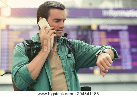 Do not have time. Pleasant adult guy with backpack is talking on mobile phone and looking at his watch while standing at internetional airport against information board. Travel concept