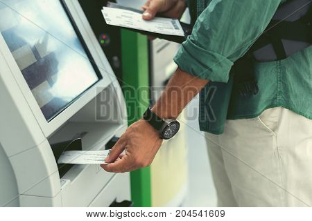 Useful service. Close-up of hands of guy with watch is standing with tickets and using self-service check-in kiosk for printing his boarding pass at modern airport building
