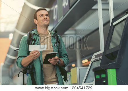 Feeling of joy. Positive adult man with backpack is standing at modern airport and holding his boarding pass while looking up with smile. Copy space in the right side