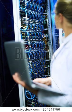 Unrecognizable female scientist working with supercomputer, focus on server cabinet with wires in background