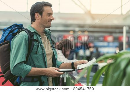 Happy trip. Profile of joyful man with backpack is standing near registration desk in international airport and holding his ticket with smile. Copy space in the right side