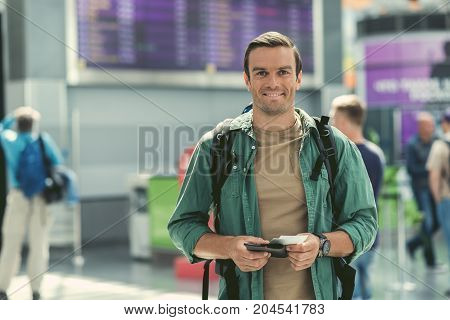 Feeling excited. Portrait of delightful pleasant adult man with backpack is standing at international airport with tickets. He is looking at camera with joy. Copy space in the left side
