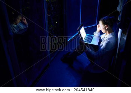 High angle portrait of beautiful young woman sitting on floor in dark server room using laptop while working with supercomputer at night