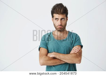 Close up isolated portrait of unhappy hispanic guy in trendy clothes and haircut, looking away, pursuing lips expressing insult and dissatisfaction. Human emotions. Copy space