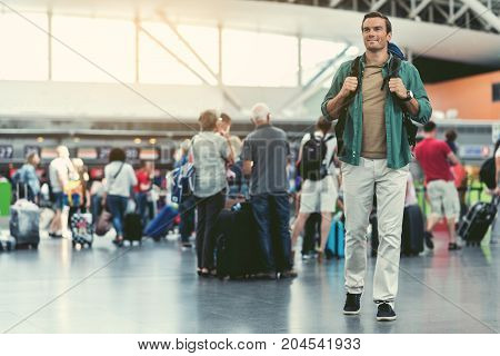 Summer vacation. Full-length of young man with backpack is standing in hall of international airport with passengers on background. He is looking aside with smile. Copy space in the left side