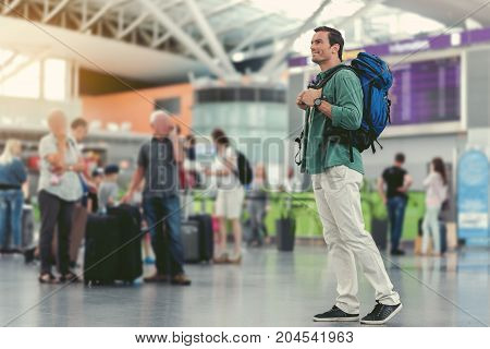 Always positive. Full-length of adult guy with backpack is standing in hall of modern airport with passengers on background. He is expressing happiness. Copy space in the left side