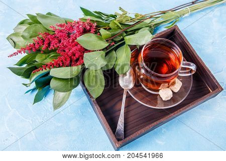 Picture of black tea, red flowers, sugar on wooden tray