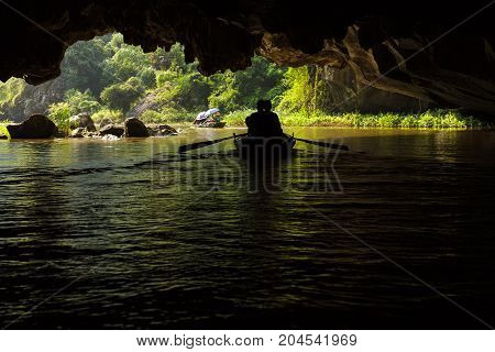 Two Boats Pass Through A Flooded Cave At Trang An Unesco World Heritage Site In Ninh Binh, Vietnam