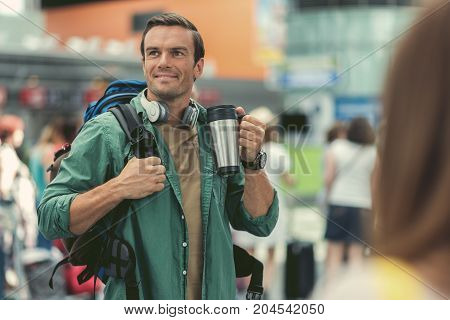 Enjoying coffee. Positive adult guy is drinking espresso and looking aside with smile while standing at modern airport with backpack and headphones on his neck. Copy space in the right side