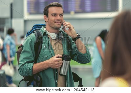 Pleasant conversation. Selective focus portrait of happy mature guy is making call using smartphone while drinking coffee. He is standing at modern airport with backpack and headphones