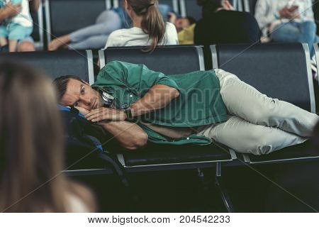 Feeling tired. Selective focus of exhausted guy is lying on bench and waiting for his flight at international airport. He is looking at camera wearily