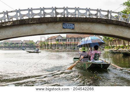 NINH BINH VIETNAM - 5/6/2016: Boats on the Ngo Dong River entering Tam Coc village at the Trang An UNESCO World Heritage site in Ninh Binh Vietnam.