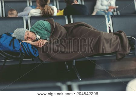 Cute adult man is napping on chairs while waiting for flight. He is lying on backpack wearing hat and covering with plaid. Passengers are on background