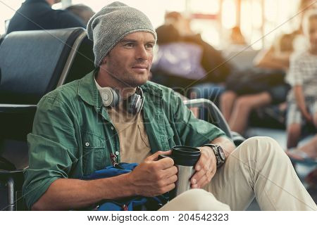 Need coffee. Serious stylish guy with hat and headphones is sitting on floor at waiting room and drinking beverage. He is looking aside thoughtfully
