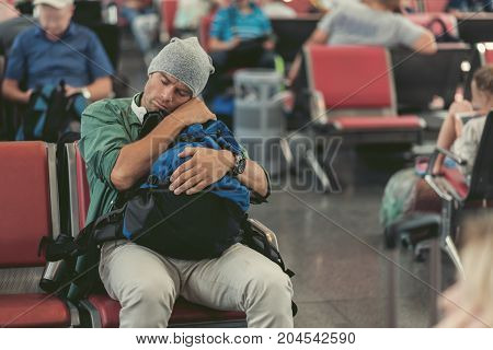 Exhausted stylish young man is sitting on red chairs of airport lounge and sleeping while waiting for his flight. He is holding backpack on knee. Copy space in the right side