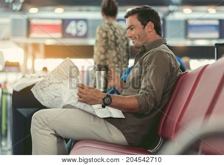 My favorite place. Profile of cheerful young man is looking at map while sitting in international airport and drinking coffee