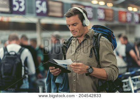 Adventure. Cheerful pleasant young man with backpack is listening to music through headphone and holding tickets while standing at airport. He is looking at boarding pass with concentration