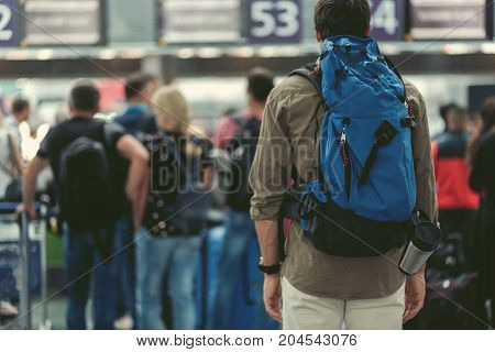 Deadly boring. Back view of adult man with backpack is standing in line at international airport. People on background. Copy space in the left side