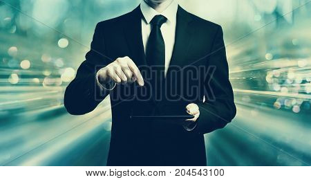 Businessman holding a tablet computer on blue tech background
