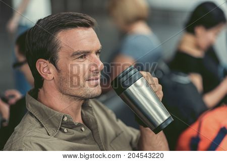 Get some energy. Close-up of face of positive bristled young man is drinking coffee while sitting at airport lounge. He is looking aside with smile