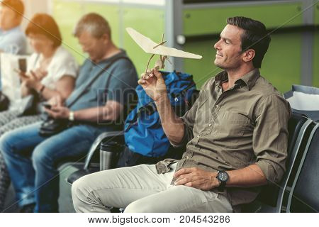 Cute toy. Profile of cheerful young man is holding wooden model of hang glider while sitting on bench at airport lounge with passengers on background. Copy space in the left side