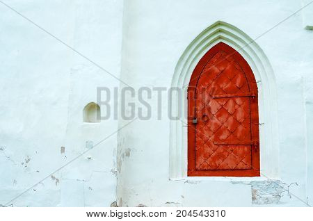 Architecture background. Aged dark red metal forged door with arcade on the white stone wall. Architecture details. Vintage architecture background with old metal door. Architecture