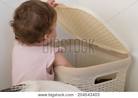 child climbs in laundry basket. back view