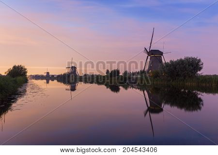 Windmills of Kinderdijk a world heritage site of UNESCO are lined up at the waterside at sunset. Besides windmills the site shows various other features important for water management such as dykes pumping stations and reservoirs.
