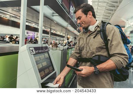 Cheerful young male passenger with backpack and headphones on his neck is standing near self-service check-in kiosk at international airport building with smile. He is printing his boarding pass