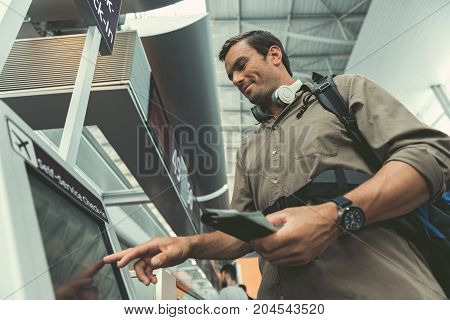 Low angle of joyful adult male traveler is touching screen of self-service check-in kiosk at international airport building. He is standing with backpack and holding his tickets