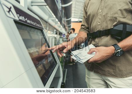 Close-up of hands of male passenger is using interactive display of self-service check-in kiosk. He is standing at international airport and holding his tickets