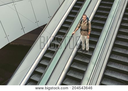 Top view of positive man with backpack wearing casual clothes is getting down on escalator at modern airport. He is looking at camera with joy. Copy space in the left side