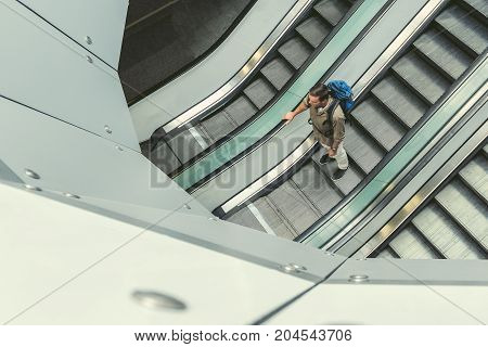 Top view of adult guy with backpack is getting down on escalator at international airport. Copy space in the left side