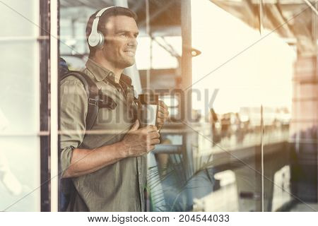 Sunset. Happy adult man with backpack is listening to music through headphones. He is standing at airport lounge and expressing gladness. Copy space in the right side