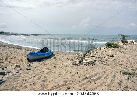 Albania. Beach on the Adriatic Sea in the Golem area a blue kayak boat stands on the shore