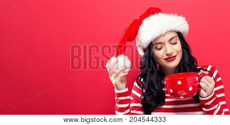 Happy young woman with Santa hat drinking coffee