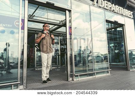 Sunny day. Joyful adult guy in sunglasses is going out of doors from terminal. Copy space in the right side