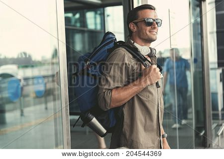 Enjoying summer. Delightful stylish guy in sunglasses is exiting from airport building. He is carring backpack and expressing gladness