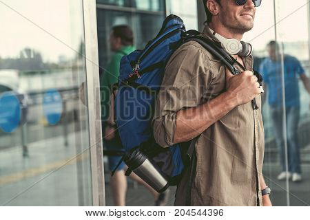 Wonderful day. Cute young man with backpack and sunglasses is going out of doors. He is expressing happiness. Copy space in the left side