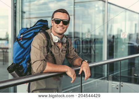 Summer vacation. Portrait of delightful man in sunglasses is looking at camera with joy. He is leaning on railing while standing outdoors with smile. Copy space in the right side