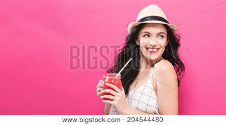 Happy young woman drinking smoothie on a pink background
