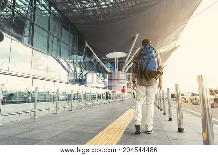 Modern tourist. Back view of adult man with backpack is walking along road near airport. Copy space in the left side