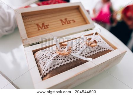 A Pair Of Golden Wedding Rings Lying In A White Wooden Box. Wedding Decoration. Symbol Of Family, Un