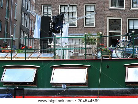 Houseboat docked on the water canal in Amsterdam, Netherlands.